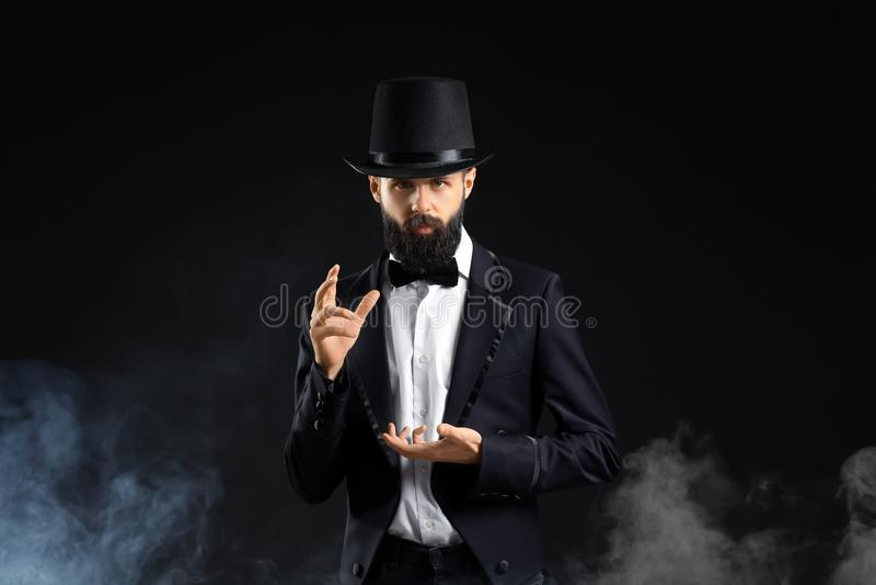 Tovenaar die trucs in rook op donkere achtergrond tonen stock fotografie