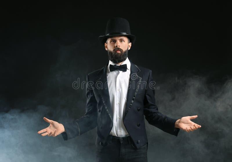 Tovenaar die trucs in rook op donkere achtergrond tonen royalty-vrije stock fotografie