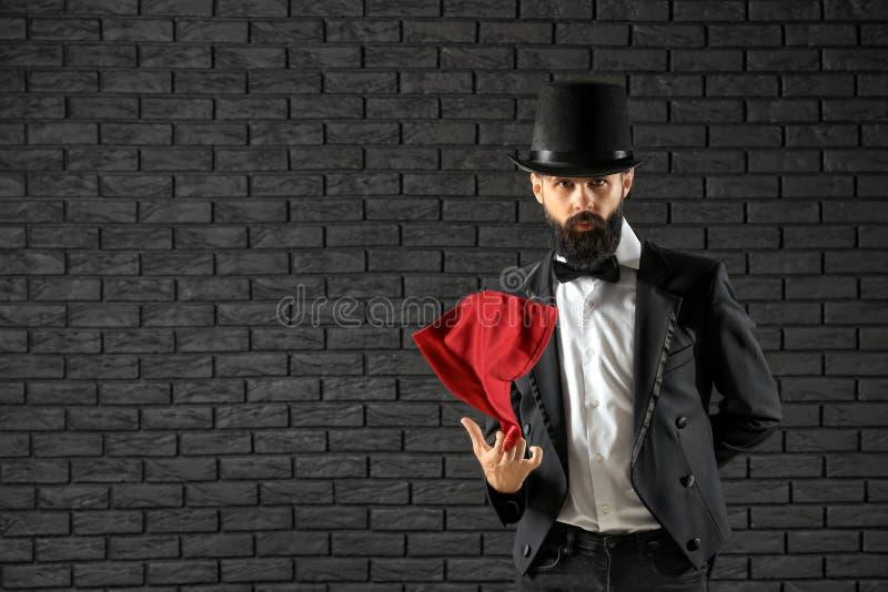 Tovenaar die trucs tonen tegen donkere bakstenen muur royalty-vrije stock afbeelding