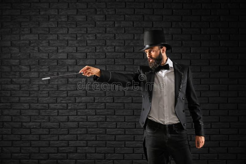 Tovenaar die trucs tonen tegen donkere bakstenen muur stock afbeelding