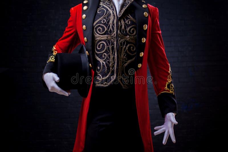 tovenaar Het close-up van dient handschoenen in de kerel in rode camisole en de cilinder stock foto