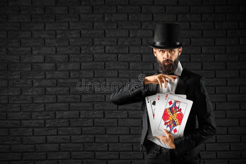 Tovenaar met kaarten tegen donkere bakstenen muur royalty-vrije stock fotografie