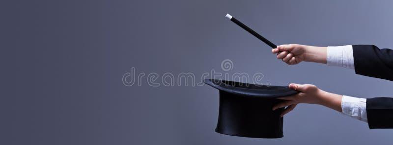 Tovenaarhanden met hoed en toverstokje stock foto's