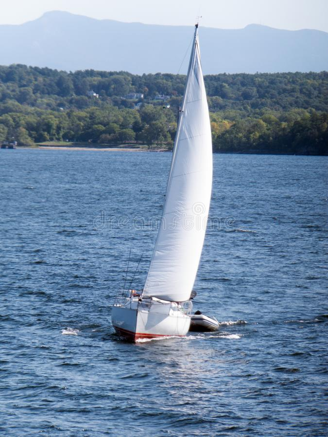 Tow Boat. Approaching sail boat towing a dinghy in Lake Champlain near Burlington, VT royalty free stock photo
