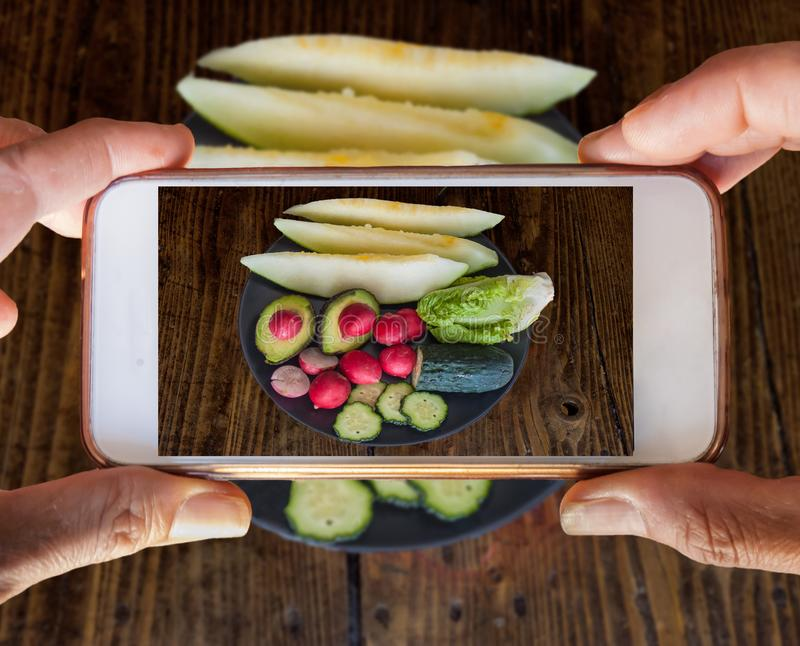 Tow hands holding a mobile phone taking a photography of vegetables and fruits. Two hands holding a mobile phone taking a photography of vegetables and fruits stock photo
