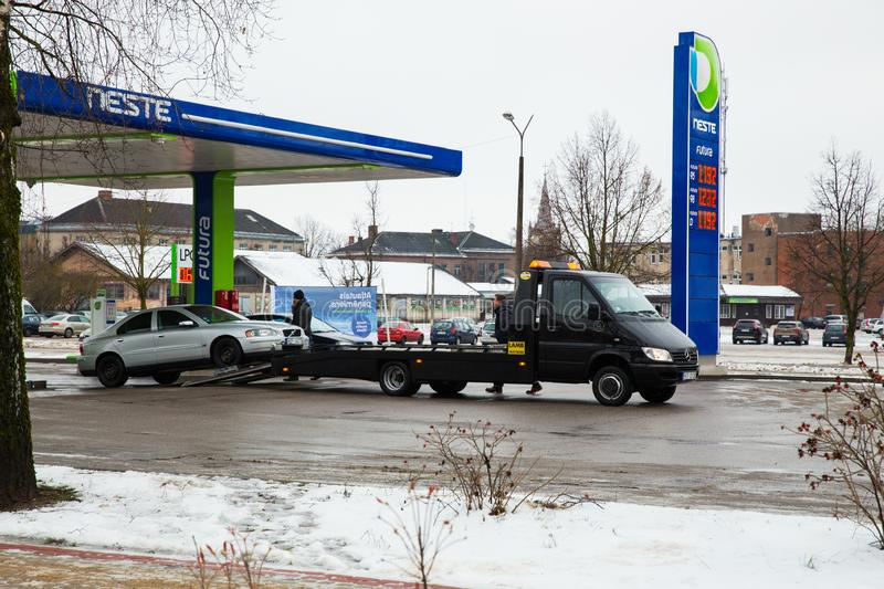 Tow truck and broken volvo car at street. winter and snow, fuel station. Urban travel photo 2018 royalty free stock photo