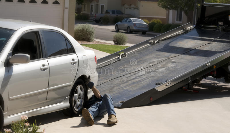 Tow-truck picking up broken down car stock images