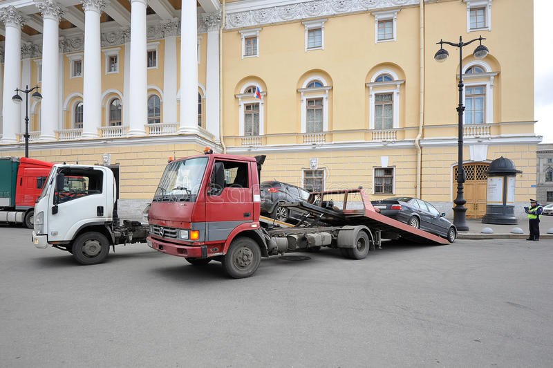 Tow truck takes cars under the supervision of the police. St.Petersburg, Russia - April 23, 2016: tow truck takes cars under the supervision of the police stock image