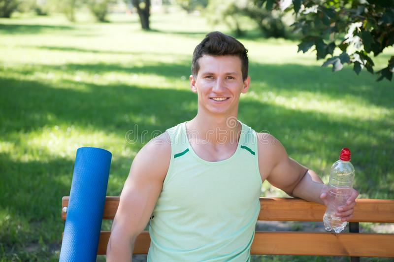 Towards healthier lifestyle. Man smiling face with yoga mat and water bottle sit on bench in park. Join outdoors yoga. Practice. Athlete with yoga equipment stock photography