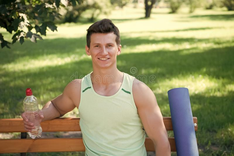 Towards healthier lifestyle. Man smiling face with yoga mat and water bottle sit on bench in park. Join outdoors yoga. Practice. Athlete with yoga equipment stock image