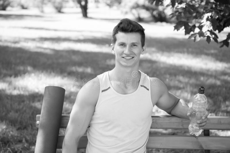 Towards healthier lifestyle. Man smiling face with yoga mat and water bottle sit on bench in park. Join outdoors yoga. Practice. Athlete with yoga equipment royalty free stock photo