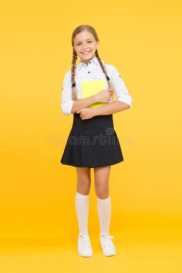 Towards knowledge. small girl in school uniform. dictionary notebook. Get information. reading story. childrens. Literature. kid learning grammar. back to stock images