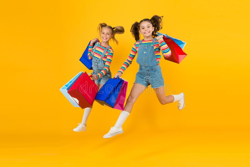 Towards purchase. Modern fashion. Kids fashion. Cute children hurry up for sale season. Discount and sale. Little girls. Carry shopping bags. Matching outfits stock image