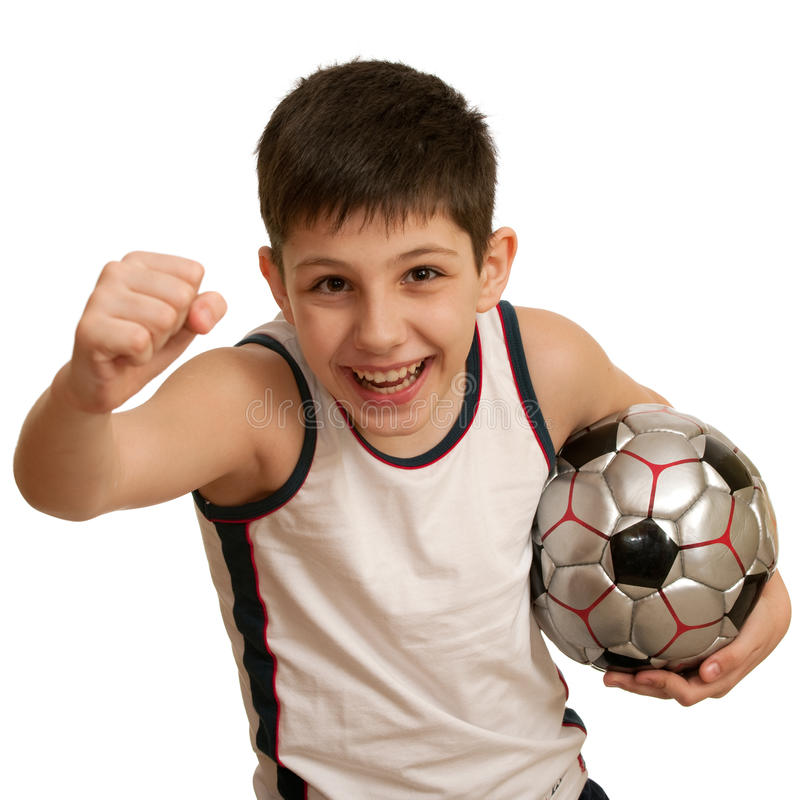Towards the victory. A running teen holding his right fist up and with a football ball in his left hand; isolated on the white background royalty free stock images