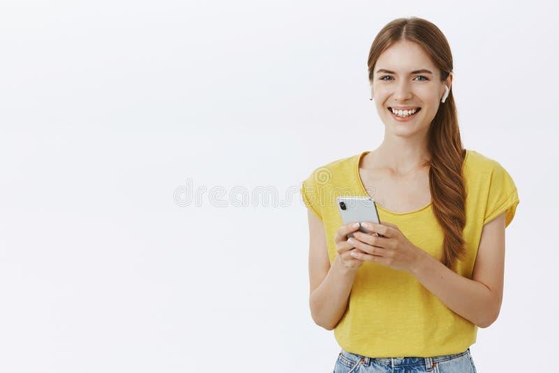 Towarzyski przyglądający szczupły śliczny kobieta model z warkoczem jest ubranym bezprzewodowe słuchawki opowiadać na telefonu mi obrazy royalty free