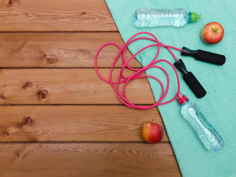 Towel, bottle of water apples and skipping rope on wooden table. Fitness concept with towel, bottle of water apples and skipping rope on wooden table background stock images