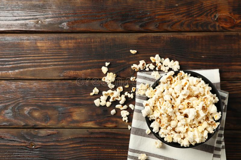Towel and bowl with popcorn on wooden background. Copy space royalty free stock images