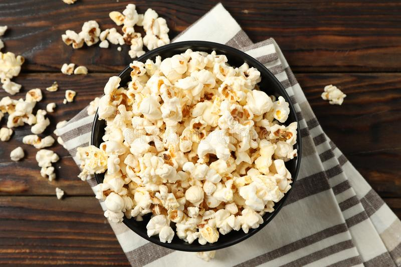 Towel and bowl with popcorn on wooden background. Top view royalty free stock photography