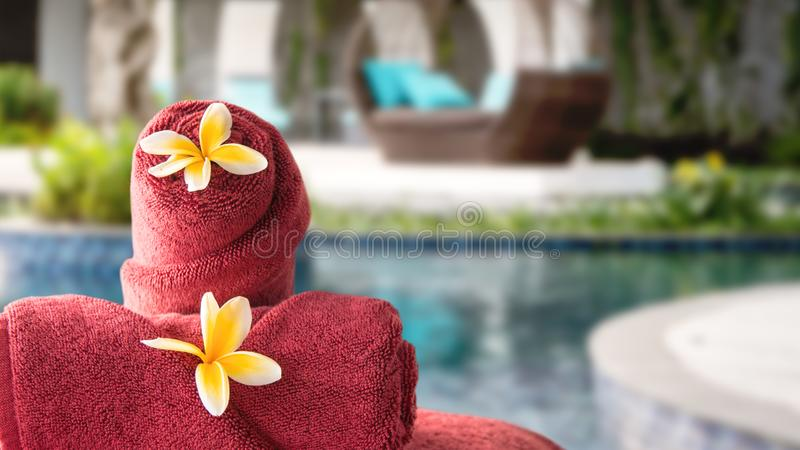 Towel and flowers on outdoor chair at resort spa with pool and garden in the background royalty free stock photo