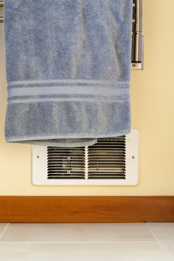 Towel hanging in front of in-wall electric baseboard heater heating unit. Dangerous house home fire hazards. Towel hanging in front of in-wall bathroom electric royalty free stock images