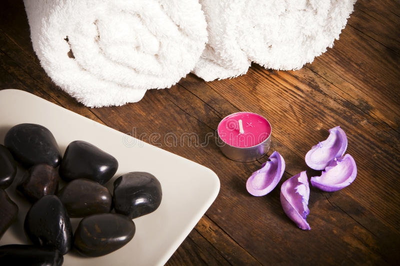 Towel next to candles and pebbles. royalty free stock image