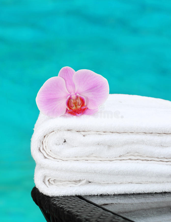 Towel with orchid poolside. Clean towel with orchid poolside royalty free stock photo