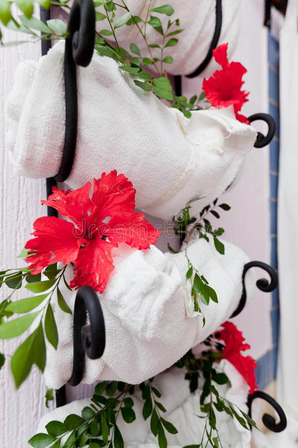 Towel rack. At the spa with fresh hibiscus flowers and green leaves royalty free stock photography