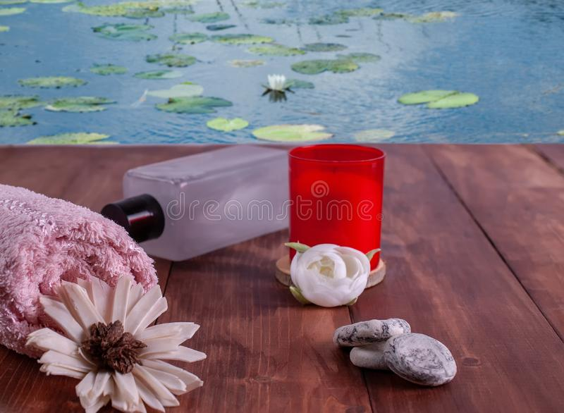 Towel, stones, oil and red candle stock image