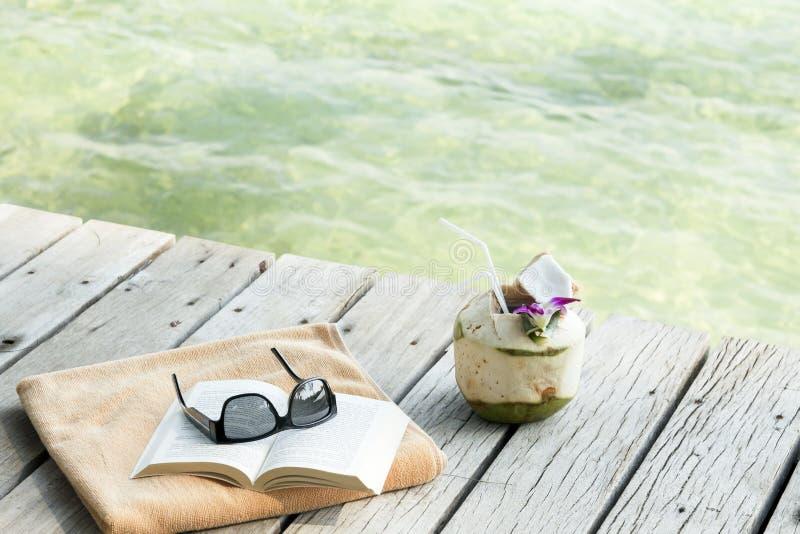 Towel sunglasses book longdrink on pier Koh Samui Thailand stock photography