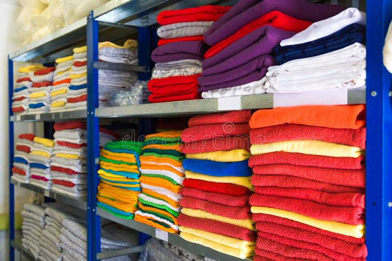 Towels, bed sheets and clothes on the shelf stock images