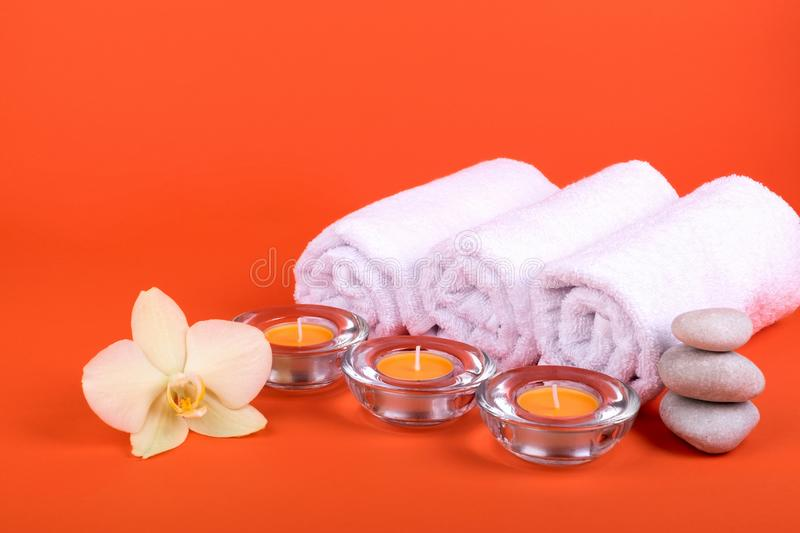 Towels, candles and orchid flowers for a spa relaxation on orange background stock photography