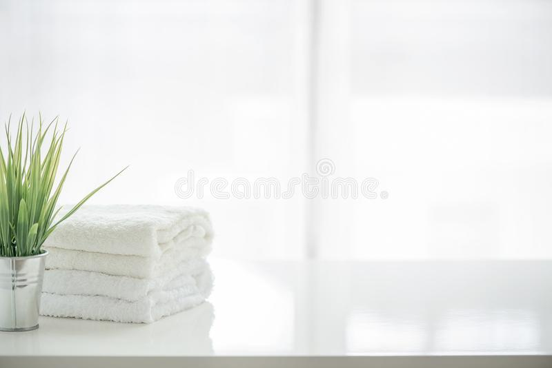 Towels and houseplant on white table with copy space stock photos
