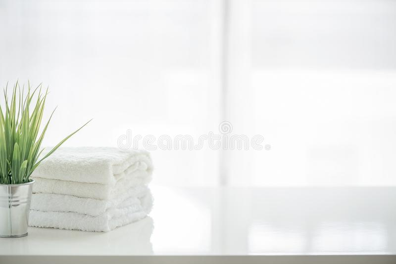 Towels and houseplant on white table with copy space stock photography