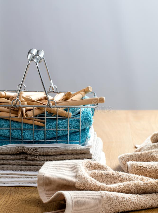 Towels with wooden clothing pins for laundry and hygiene concept. Pile of cotton towels with wooden clothing pins in basket for laundry and hygiene concept over stock photo