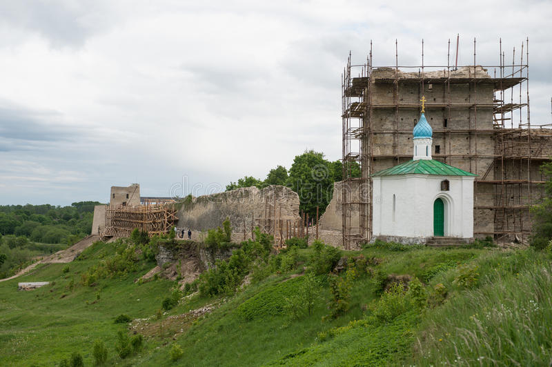 Tower of ancient Izborsk fortress. Of the 15th century on a sunny day during reconstruction and restoration works stock photo
