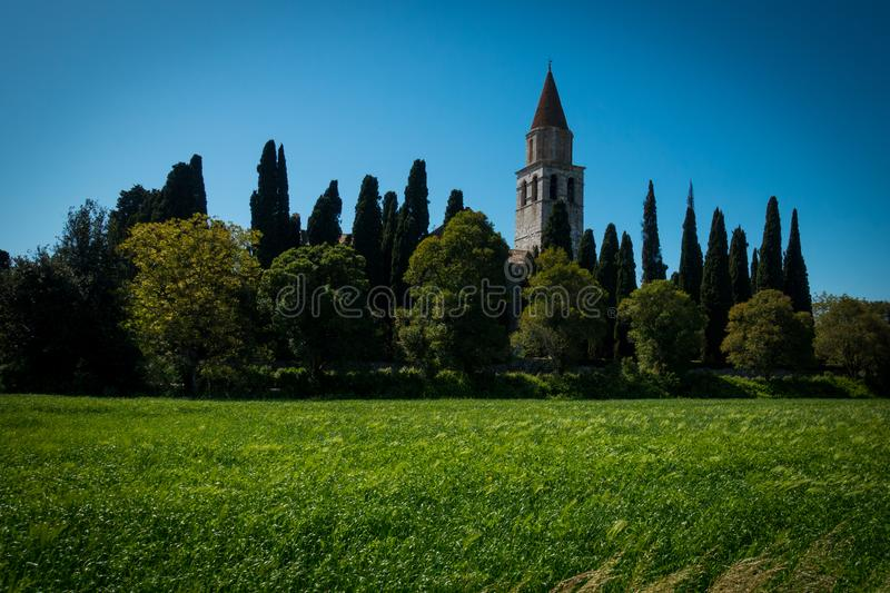 Tower of Basilica di Aquileia in Italy with meadows, trees, cypress and clear blue sky stock photo