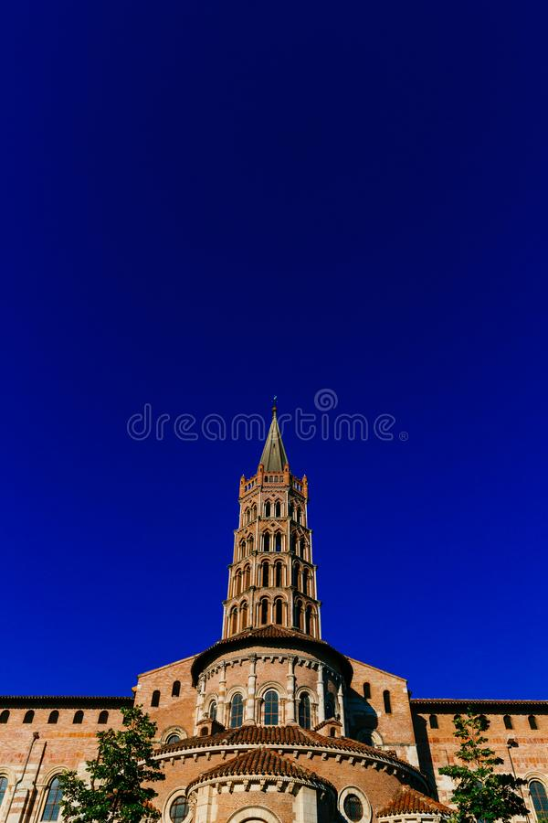 Tower of Basilica of Saint-Sernin against blue sky, in old town of Toulouse, France royalty free stock photography