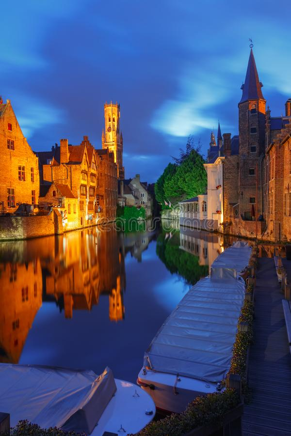 Tower Belfort from Rozenhoedkaai in Bruges. Scenic cityscape with a medieval fairytale town and tower Belfort from the quay Rosary, Rozenhoedkaai, at night in stock photography