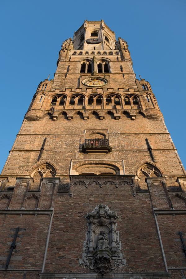 The tower of the Belfry Belfort on Grote Markt square in Bruges, Belgium. Closeup of the tower of the Belfry Belfort on Grote Markt square in Bruges, Belgium stock photo