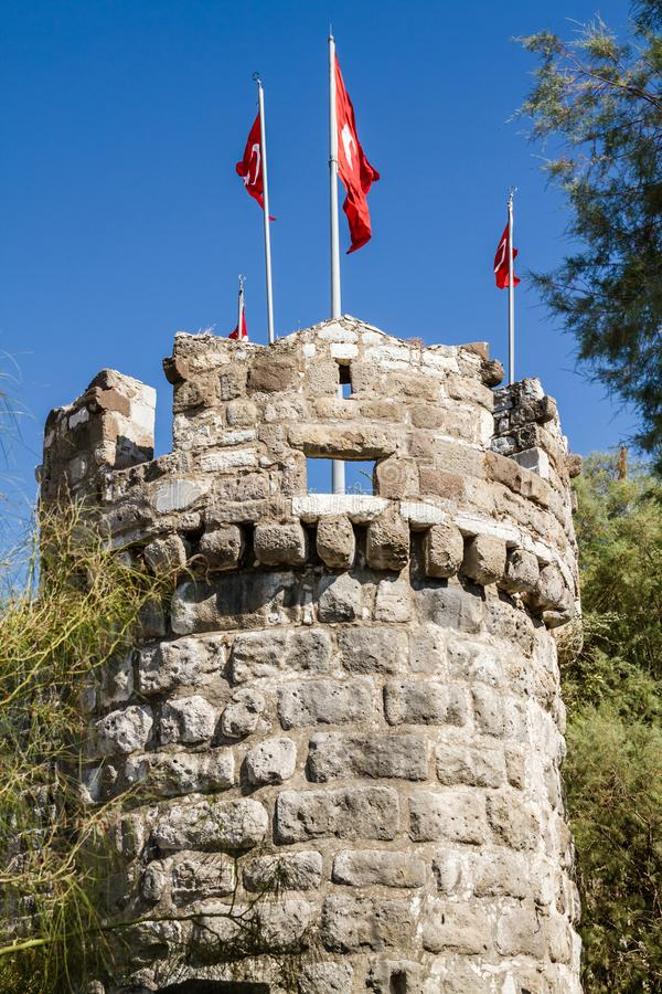 Tower of Bodrum Castle with Turkish Flags. On pole against blue sky stock photo