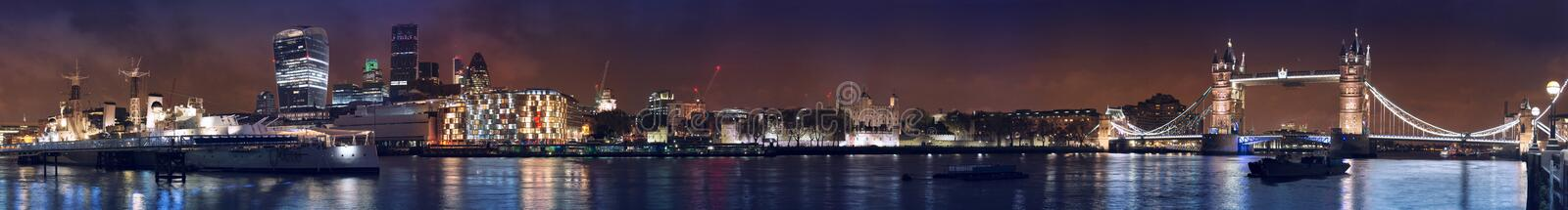 Tower bridge, financial district and warship museum wide panorama. Very wide night panorama of London Tower bridge, Tower, financial City district and HMS royalty free stock image