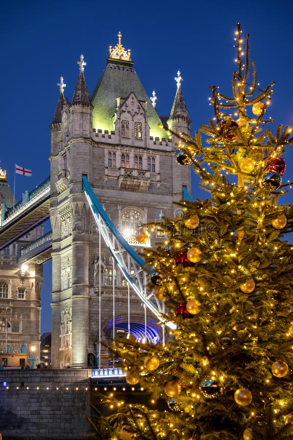 The Tower Bridge of London, United Kingdom, with a Christmas tree. The Tower Bridge of London, United Kingdom, with a festively decorated Christmas tree in front stock photo