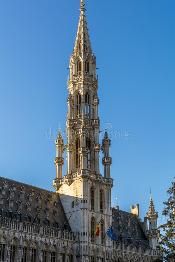 The tower of The Brussels Town Hall in Brabantine Gothic style with lavishly pinnacled octagonal openwork. Atop the spire stands gilt metal statue of the royalty free stock photos
