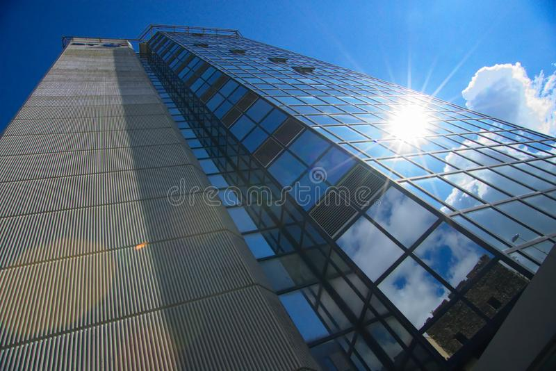 Tower building of glass in Swansea South Wales. Sun reflecting off a towering building in Swansea, South Wales United Kingdom with swansea castle reflected in stock images