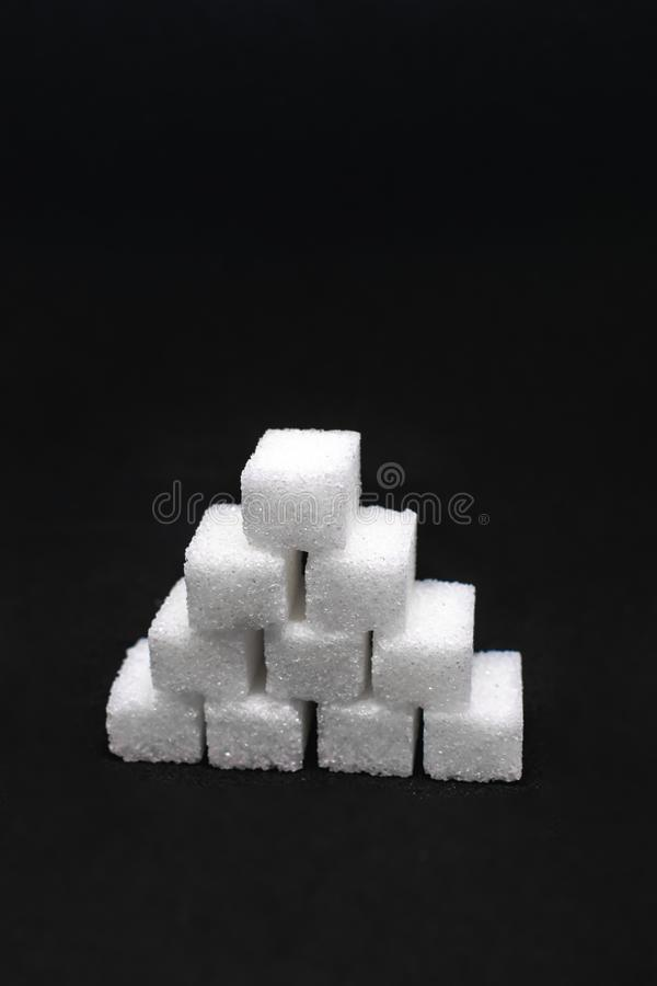 Tower built out of sugar white cubes on isolated black background. Tower built out of sugar white cubes on an isolated black background with blank space royalty free stock images