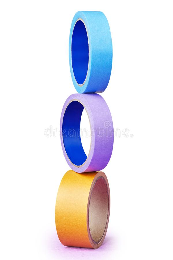 Tower built of three poised multi-colored rolls of adhesive tap stock photography