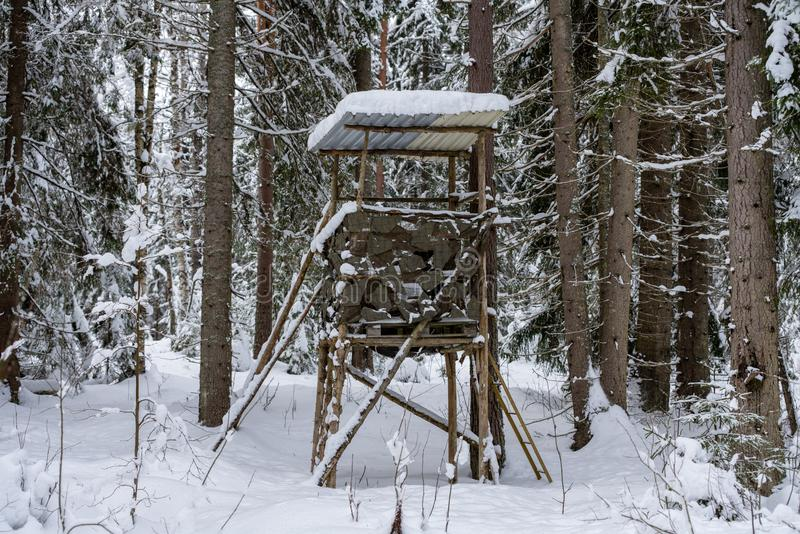 Hunters nest or tower in the middle of the forest in winter stock photography