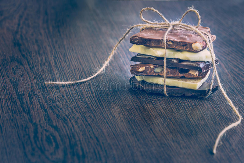 A tower of chocolate bars wrapped like a chocolate present . Various chocolate pieces over dark wood background. A tower of chocolate bars wrapped like a royalty free stock photo