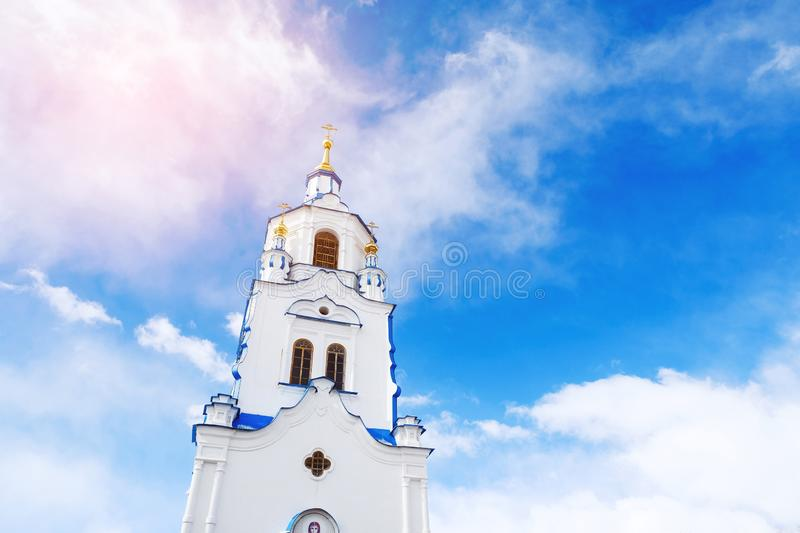 The tower of Church on background of blue sky with clouds. Russia, Tyumen royalty free stock photography