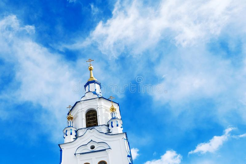 The tower of Church on background of blue sky with clouds. Russia, Tyumen stock photo
